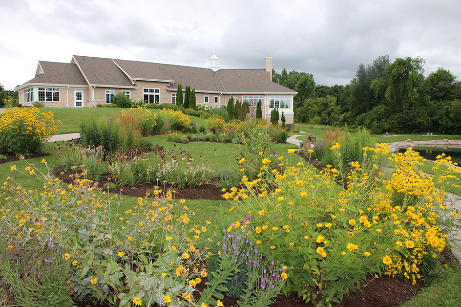 Jack and Engrid Meng hospice residence with landscaped flower gardens along scenic walking path.