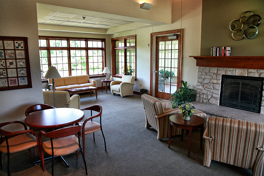 Jack and Engrid Meng hospice residence community area with sitting areas and inviting fireplace.