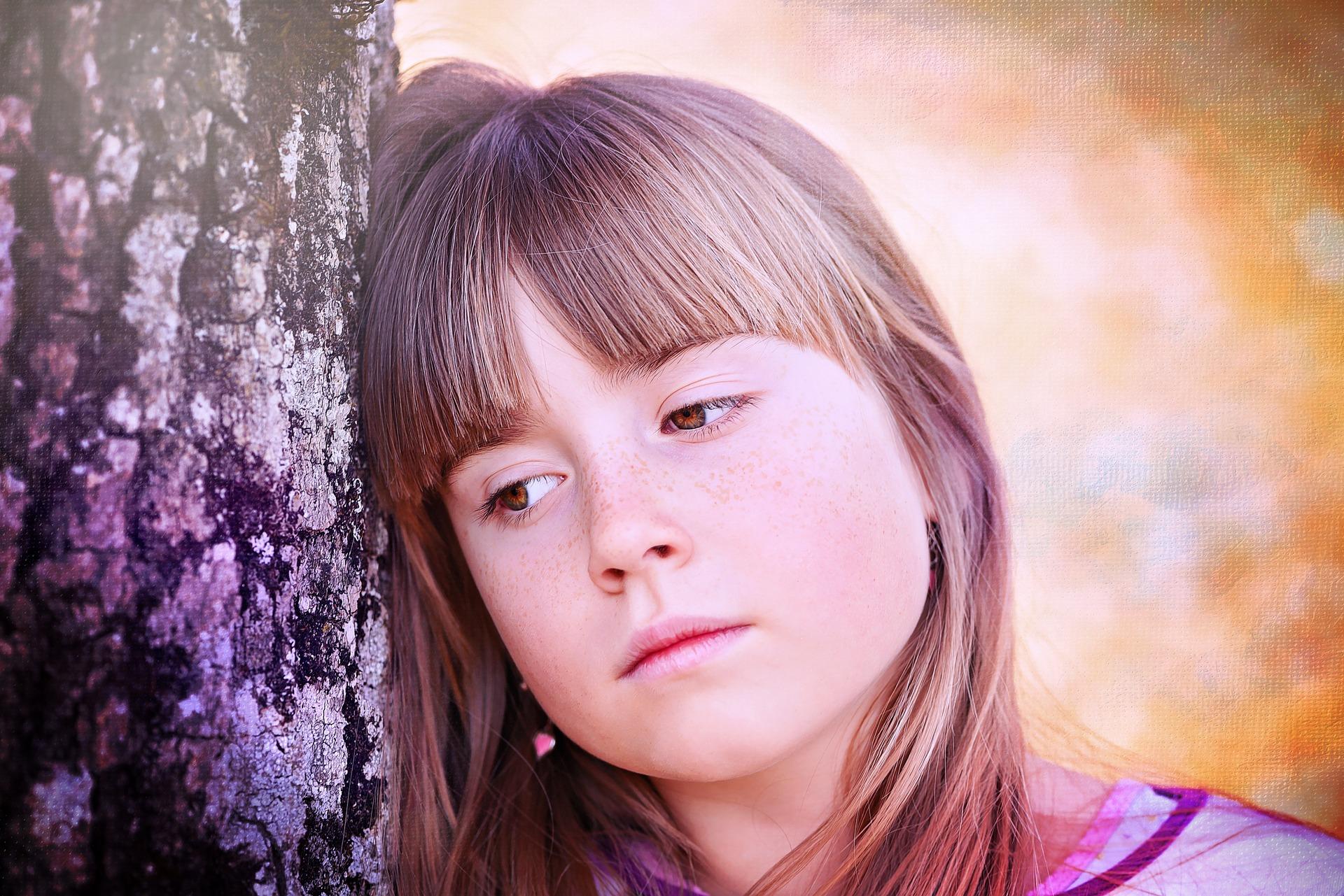 Sad child by tree
