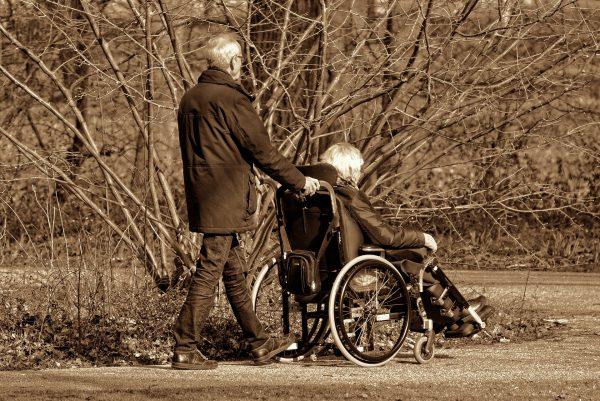 Man pushing woman in wheelchair